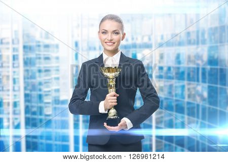 Portrait of businesswoman keeping golden cup, blue background. Concept of victory and success