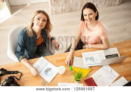 We like our work. Beautiful young two women are working in office. They are sitting at desk and smiling. The ladies are looking at camera happily