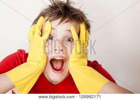 Screaming Child In Gloves With Hands On Face