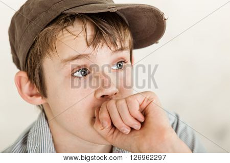Anxious Poor Child With Hand Near Mouth