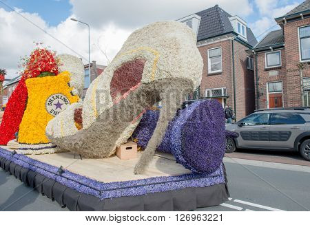 HILLEGOM, THE NETHERLANDS - APRIL 23, 2016: Moving platform with a huge frame made in a form of boots and shoes decorated with spring flowers.Taking part in the  flowers parade