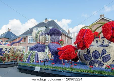 HILLEGOM, THE NETHERLANDS - APRIL 23, 2016: Moving platform with a frame made in a form of a traditional Dutch kissing couple and tulips. Taking part in the  traditional flowers parade