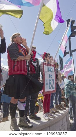 Asheville, North Carolina, USA - April 2, 2016: LGBT protest rally against the HB2 Law in North Carolina with symbolic flags, transgender symbols, and signs about bathroom restrictions, pride, and love