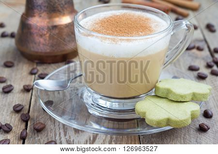 Coffee latte in glass cups with matcha cookies on a wooden table