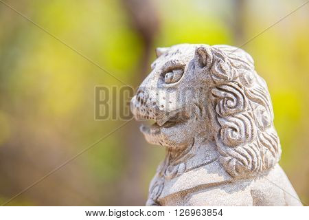 LaoshanChina 21/04/2016 Surprised looking stone lion figure outside handrail decoration in a temple in LaoshanChina on a sunny day