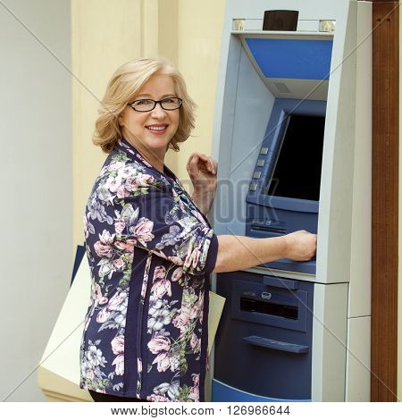 Mature blonde woman with credit card in hand near automated teller machine in shop