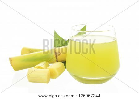 Fresh squeezed sugar cane juice in glass with cut pieces cane isolated on white background