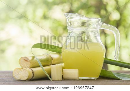 Fresh squeezed sugar cane juice in pitcher with cut pieces cane on nature background
