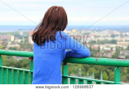 Woman watching view of the city Gdansk from observation tower woman looks at panorama of city style melancholy concept