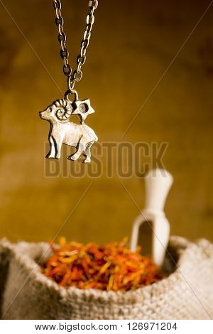 Medallion with the sign of Aries and saffron in a bag
