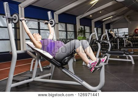 Smiling pregnant woman lifting barbell at the gym