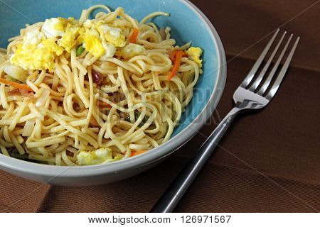Chinese noodles or chow mein with eggs and vegetables in a bowl on a napkin with copy space.