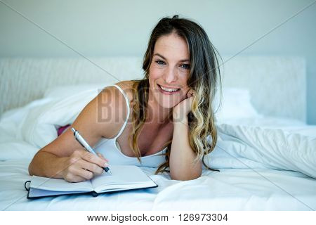 smiling woman lying in bed reading a book