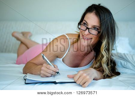 smiling woman, lying in bed with glasses on and writing in a book