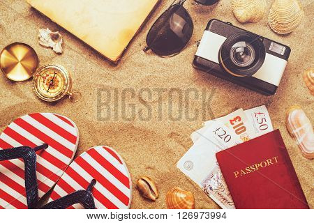 Summer vacation accessories on tropical sandy ocean beach holidays abroad - summertime lifestyle objects and Great Britain pounds in flat lay top view arrangement in warm sand.