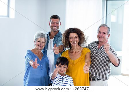 Portrait of happy family showing their thumbs up at home