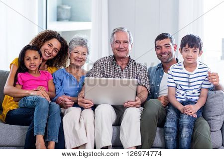 Portrait of happy family using laptop on sofa at home
