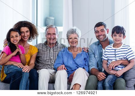Portrait of happy family sitting together on sofa at home