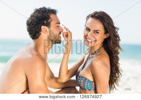 Happy girlfriend putting sunscreen on boyfriends nose on a sunny day