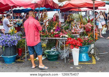 Saint-Paul Reunion Island France - December 24 2015: Florist and vendor on a local market in Saint Paul on the island of La Reunion (France) in the Indian ocean.