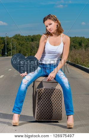 Portrait Of A Beautiful Girl Hitchhiking With Luggage