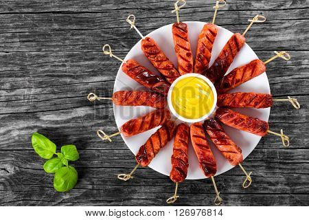 Grilled sausages on skewers on a white dish with mustard in a gravy boat on an old rustic table studio lights top view