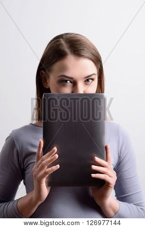 Magnetic glance. Pleasant attractive woman holding tablet and hiding her face behind it while standing isolated on grey background