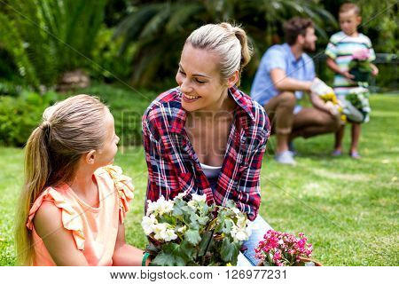 Smiling mother with flower pots looking at daughter in yard
