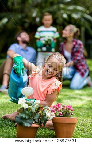 Smiling girl watering flower pots in yard
