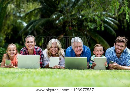 Portrait of family with technologies lying on grass at yard