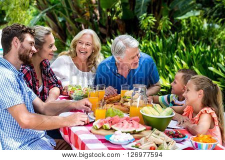 High angle view of family having food at table in yard