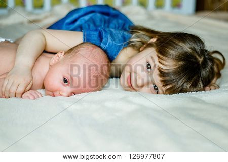 Cute little girl is playing with his younger brother at home lying on the bed