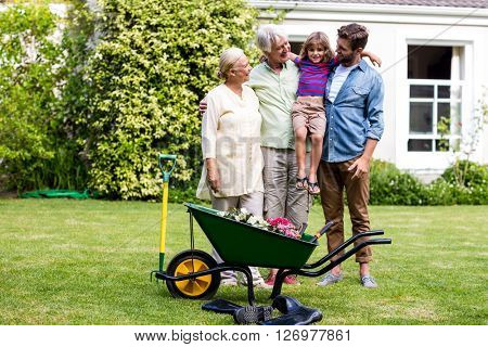Father and grandfather standing with granny carrying son at yard
