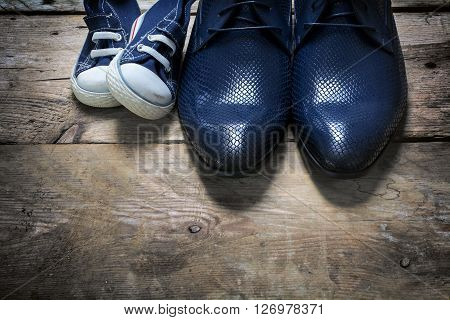 father's business shoes and kids sneakers side by side on rustic wood concept of family single parent and father's day view from above