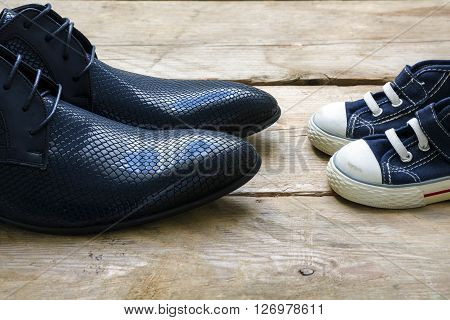 men shoes and kids sneakers standing facing each other on a rustic wooden floor concept of father's day