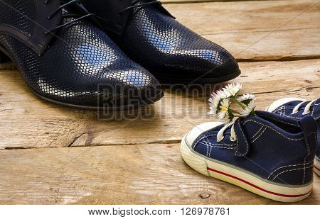 fathers day small blue kids sneakers with a bouquet of daisies standing in front of daddy's black shoes on rustic wooden planks
