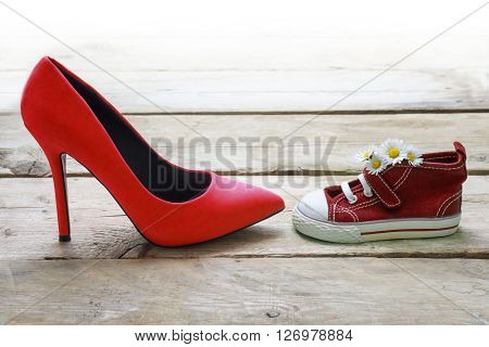 red kids sneakers with a bouquet of daisies and mum's red high heels on rustic wooden planks concept for mother's day background fades to white