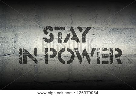 stay in power stencil print on the grunge white brick wall