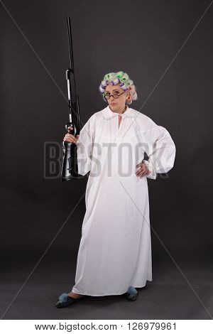 Picture of grandmother posing in full length with rifle in her hand. Beautiful elderly in defence in studio over grey background.