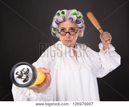 Crazy furious grandmother posing with cricket bat and lamp in studio. Senior in glasses looking at camera and defending her residence.