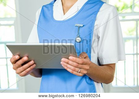 Midsection of nurse holding digital tablet at health club