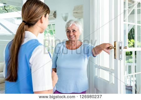 Happy aged woman standing nurse by door at health club