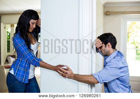 Upset couple standing on opposite sides of the wall and holding hands