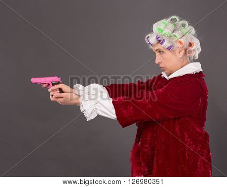 Grandmother aiming at something or someone with pink plastic gun over grey background. Profile of beautiful elderly lady in studio.