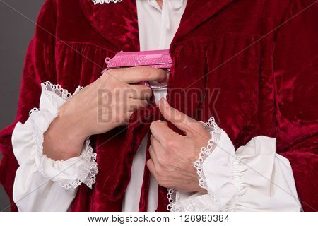 Close-up picture of woman hiding pink plastic gun under clothes. Senior lady playing in wars with weapons.