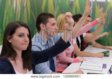 teacher teaching lessons, smart students group raise hands up in school  classroom