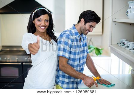 Woman showing her thumbs up while man cleaning the kitchen at home