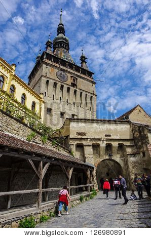 Sighisoara, Romania - May 2, 2014: Clock tower sided by old building inside medieval town of Sighisoara Transylvania Romania