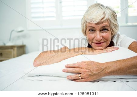 Portrait of smiling woman relaxing on bed at home
