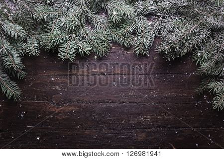 Christmas and New Year decoration composition. Top view of fur-tree branches on wooden background with place for your text.